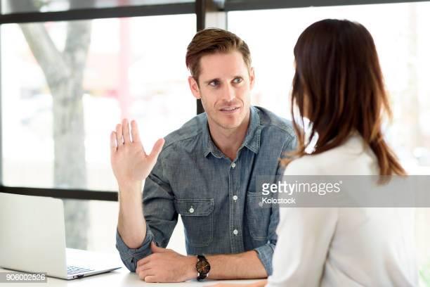 Caucasian man gesturing to woman