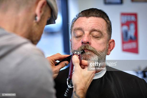 Caucasian man getting his mustache trimmed