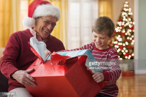 Caucasian man giving grandson Christmas gift