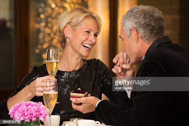 Caucasian man giving ring to wife in restaurant