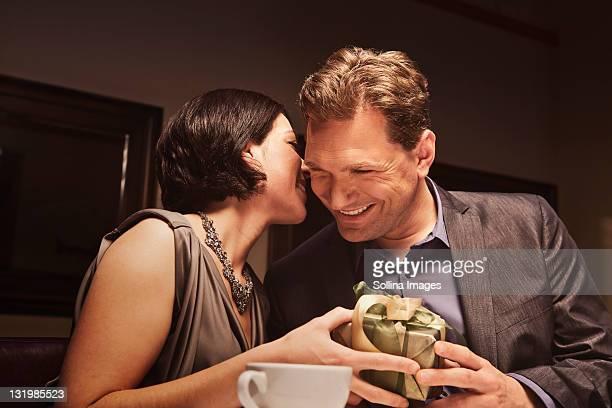 Caucasian man giving woman gift in restaurant
