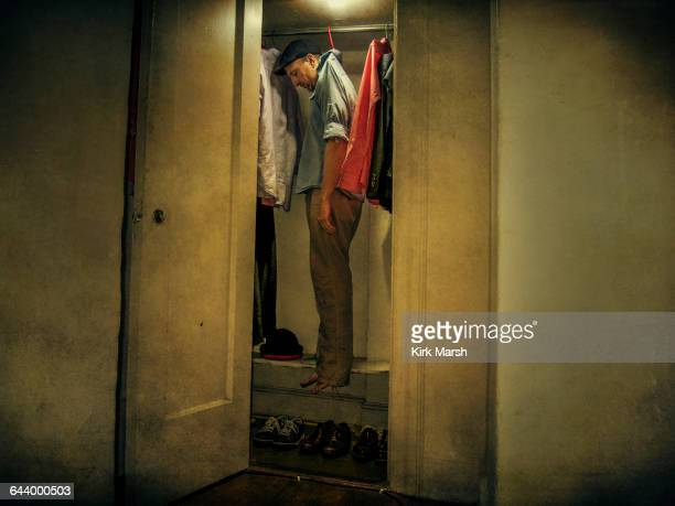 Caucasian man hanging with clothing in closet