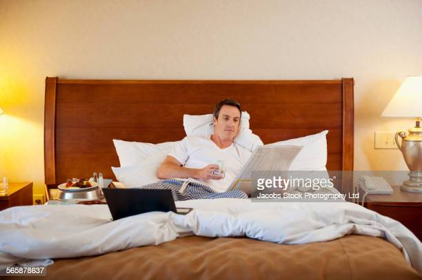 Caucasian man having breakfast in bed in hotel room