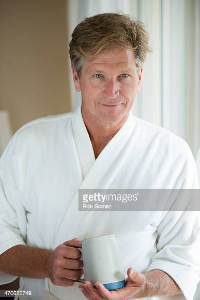 Caucasian man having coffee in bathrobe