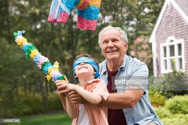 caucasian man helping grandson hit piûata - pinata stock pictures, royalty-free photos & images