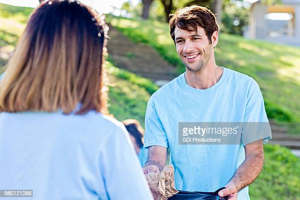 Caucasian man helps woman pick up trash in the park