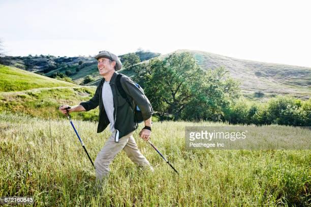 Caucasian man hiking in grass on mountain