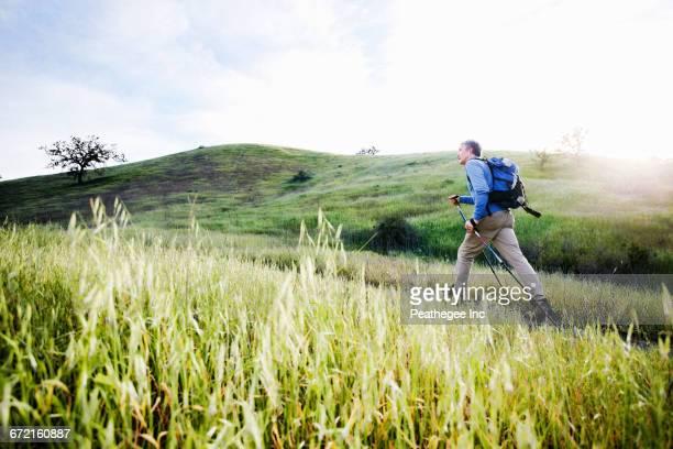 Caucasian man hiking in on mountain path