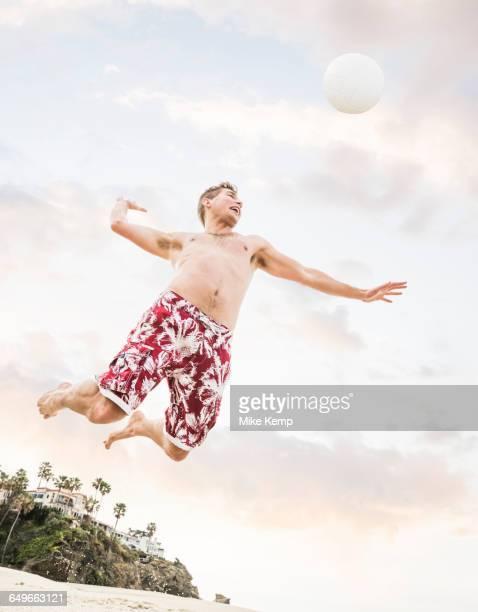 Caucasian man hitting volleyball on beach