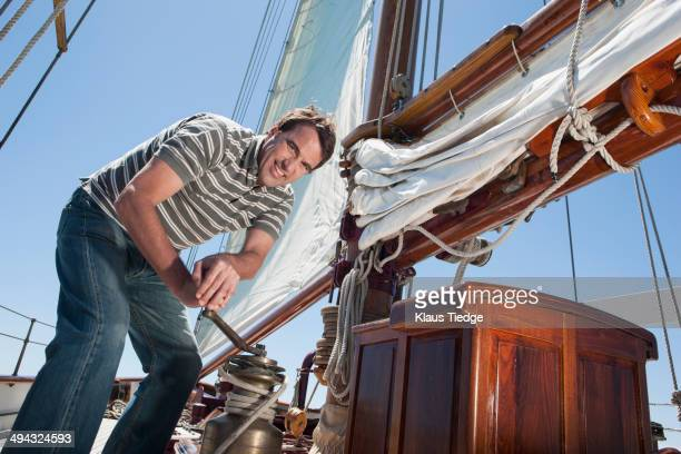 Caucasian man hoisting sail on sailboat