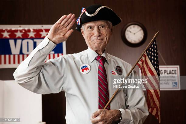 caucasian man holding american flag in polling place - us republican party stock pictures, royalty-free photos & images