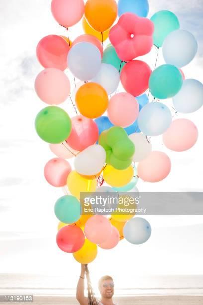 Caucasian man holding balloons on beach