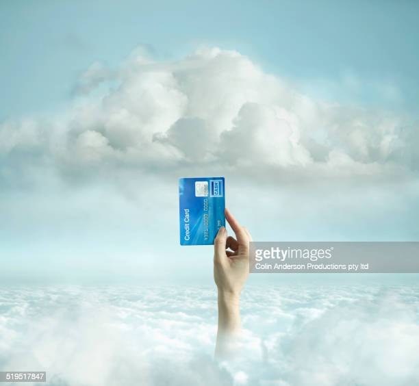Caucasian man holding credit card in clouds