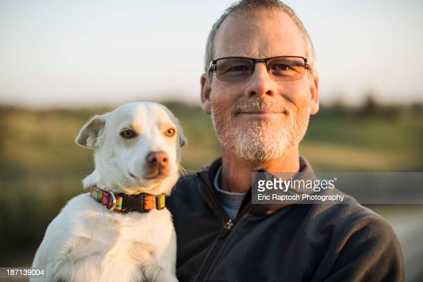 Caucasian man holding dog outdoors