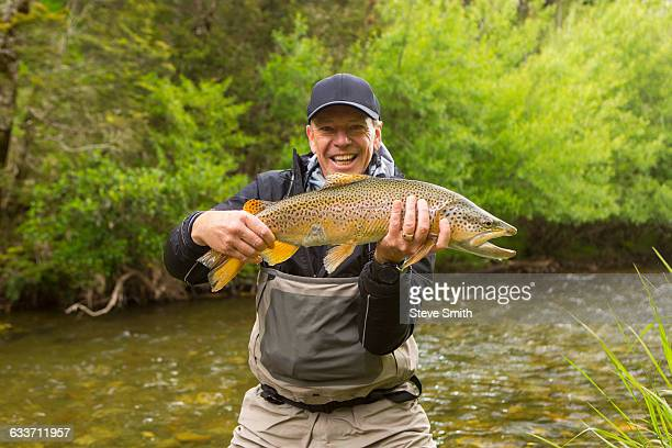 Caucasian man holding fish in remote river