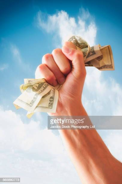 Caucasian man holding fistful of dollars against sky