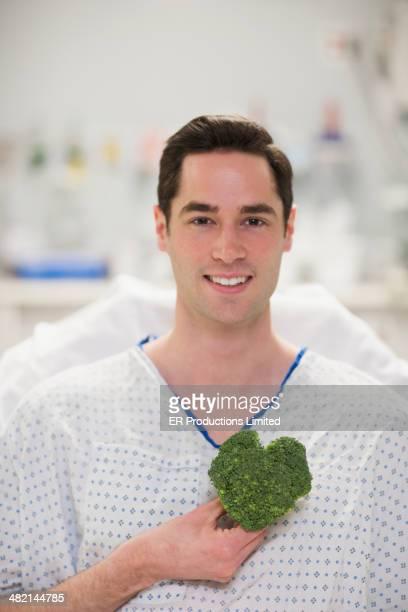 Caucasian man holding heart-shape broccoli in hospital