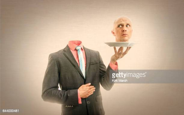 caucasian man holding his head on platter - decapitado fotografías e imágenes de stock