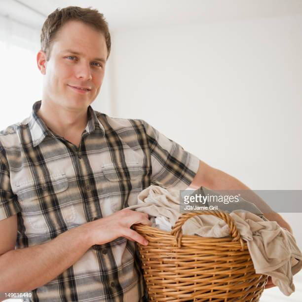 Caucasian man holding laundry basket