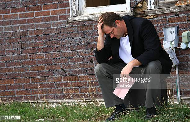 Caucasian Man Holding Pink Slip Losing Job