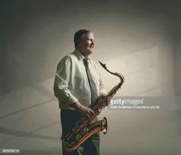 Caucasian man holding saxophone