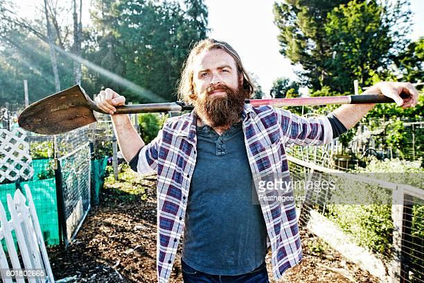 Caucasian man holding shovel in garden