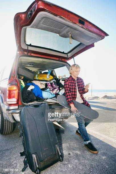 caucasian man holding skateboard and texting on cell phone - loader reading stock pictures, royalty-free photos & images