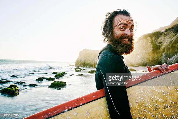 caucasian man holding surfboard at beach - leute wie du und ich stock-fotos und bilder