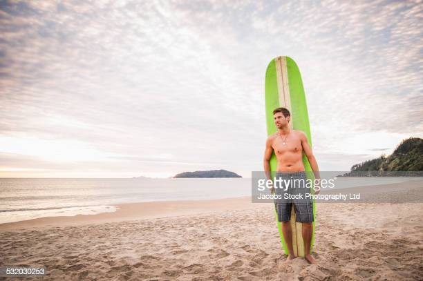 caucasian man holding surfboard on beach - whangarei heads stock-fotos und bilder