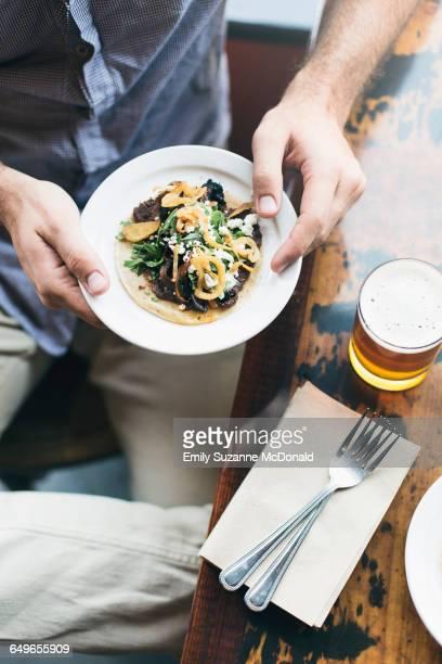 Caucasian man holding taco plate