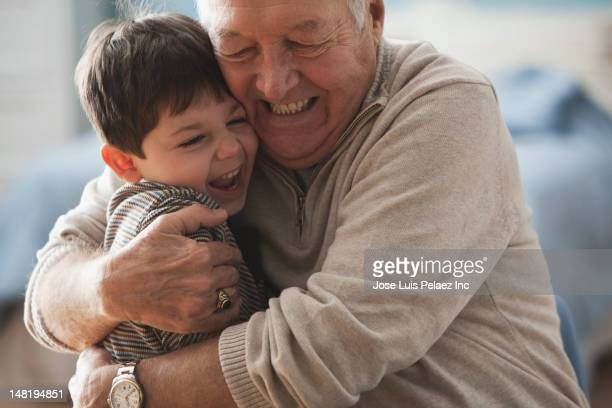 caucasian man hugging grandson - grandfather stock pictures, royalty-free photos & images