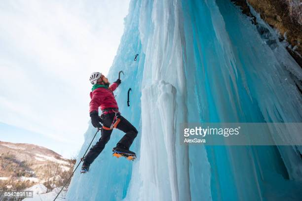 Caucasian man ice climbing on a bright winter day
