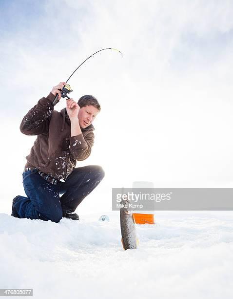 Caucasian man ice fishing