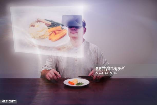 Caucasian man imagining larger meal with VR goggles