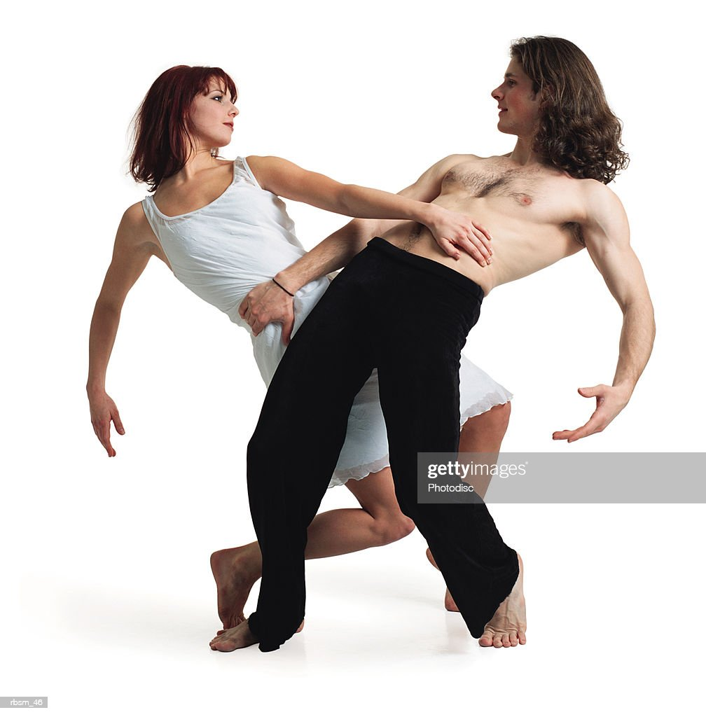 caucasian man in black pants and no shirt with caucasian woman in white dress leaning back grabbing eachother at waist and looking into eachother's eyes : Foto de stock