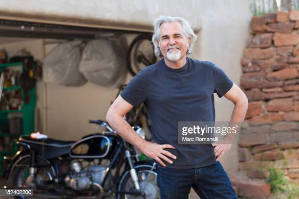 Caucasian man in driveway with motorcycle