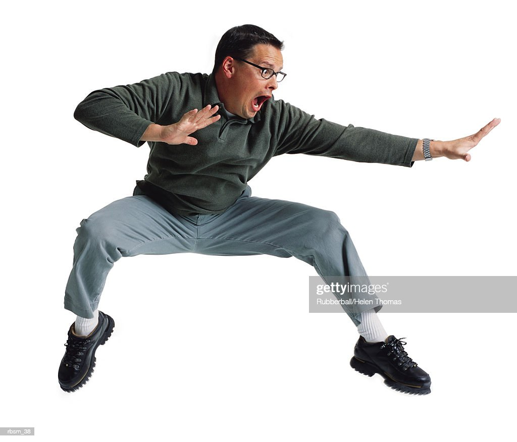 caucasian man in glasses grey pants and long sleeved polo shirt jumps back and raises his hands in a karate pose : Foto de stock