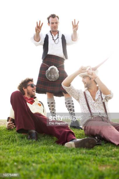 Caucasian man in kilt holding out six fingers to friends