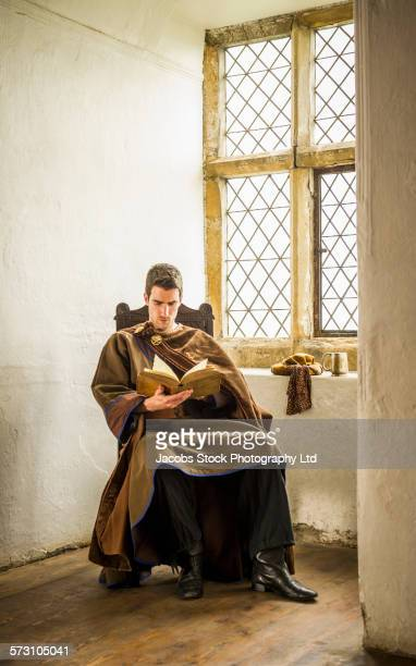 Caucasian man in medieval costume reading at castle window