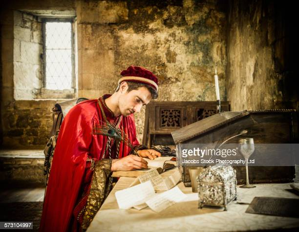 caucasian man in medieval costume reading in castle - quill pen stock photos and pictures