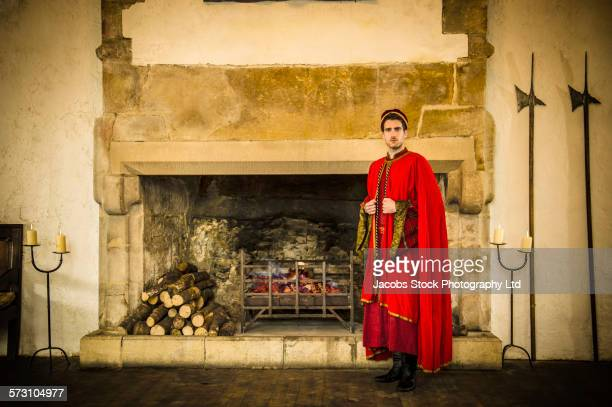 caucasian man in medieval costume standing at castle fireplace - ceremonial robe stock pictures, royalty-free photos & images