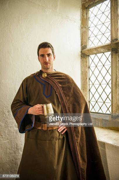 caucasian man in medieval costume standing at castle window - period costume stock pictures, royalty-free photos & images