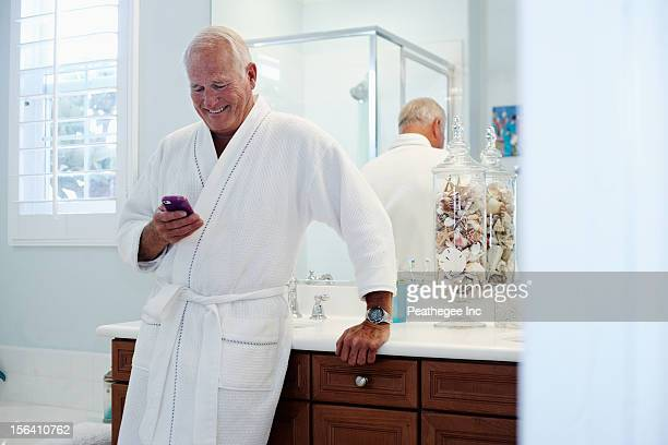 Caucasian man in robe using cell phone