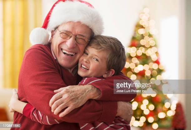 Caucasian man in Santa hat hugging grandson