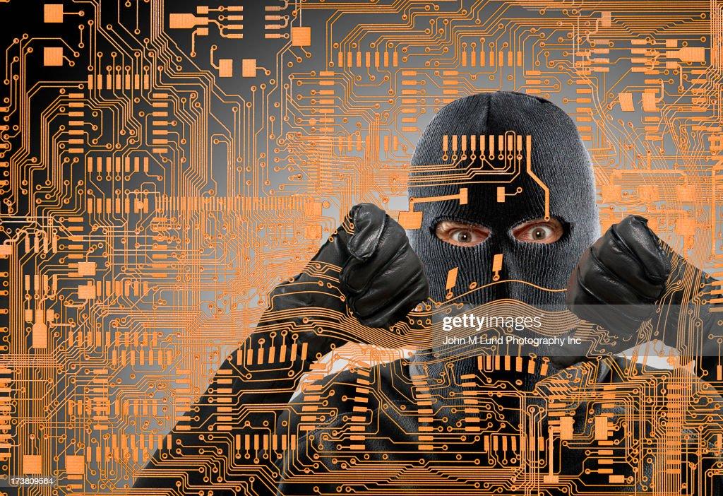 Caucasian man in ski mask behind microchip pattern : Stock Photo