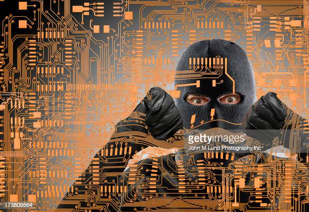 Caucasian man in ski mask behind microchip pattern