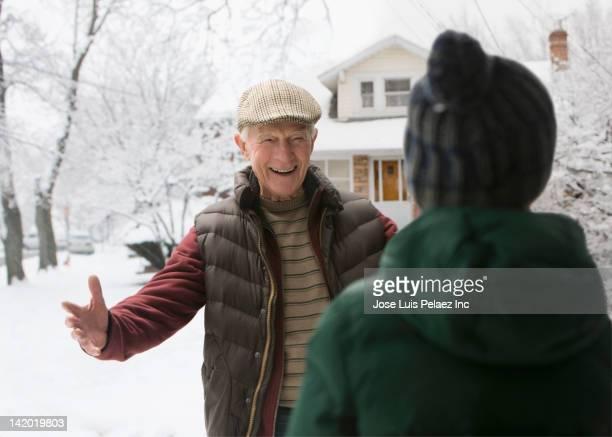 Caucasian man in snow greeting grandson