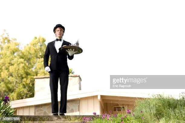 Caucasian man in tuxedo carrying tray