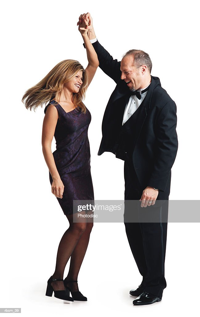 caucasian man in tuxedo spins a caucasian woman in a purple dress while the couple ballroom dances : Foto de stock