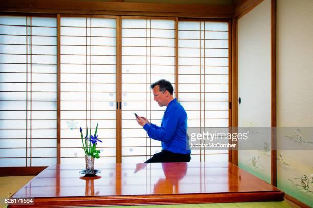 Homme caucasien dans l'utilisation de téléphone portable dans la salle japonaise